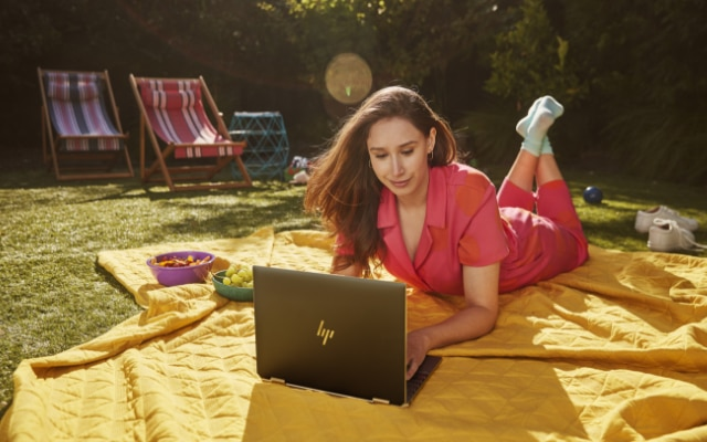 Woman working outside with an HP Spectre x360